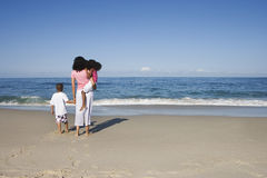 Mother and two children (5-7) standing on sandy beach, looking at Atlantic Ocean horizon, rear view Royalty Free Stock Images