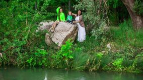 Mother And Two Children Throwing Stones Into Pond. This is a picturesque view of a family of three - mother, daughter and small son - standing and sitting on the stock video footage