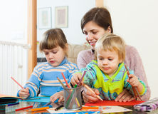 Mother and two children together with pencils Stock Photos