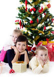 Mother with two children under Christmas tree Royalty Free Stock Photos