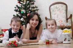 Mother and two children under Christmas tree. Smiling mother and two children under Christmas tree Stock Image