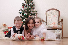 Mother and two children under Christmas trree Stock Photography