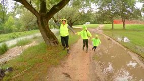 Mother And Two Children Walking In Park After Rain. The shot captured in green park at flood time - happy mother with two children - girl and little boy in stock video footage