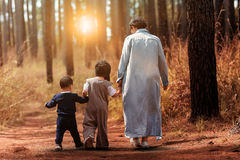 Mother and two children walking in pine wood Royalty Free Stock Image