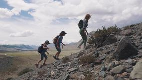 Mother and two children went Hiking in the mountains. a group of travelers up the mountain. family travelers in the. Group of travelers up the mountain. family stock video footage