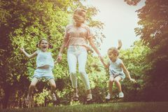 Mother with two daughter holding hands and jumping together. royalty free stock photo