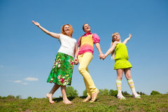 Mother and two daughter jumping on green meadow Royalty Free Stock Image