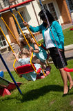 Mother with two daughters. Mother with her two daughters on a swing on sunny day Royalty Free Stock Image