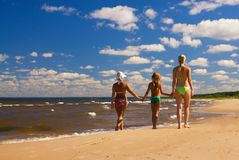Mother and two daughters. Walking on a beach near the water Stock Photography