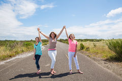 Mother and two daughters with arms raised Stock Images