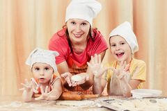 Mother with two daughters baking bread. Royalty Free Stock Photography