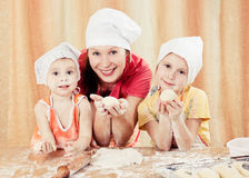 Mother with two daughters baking bread. Royalty Free Stock Images