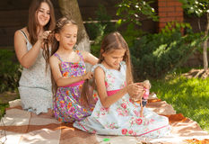 Mother and two daughters braiding hair to each oth Stock Image
