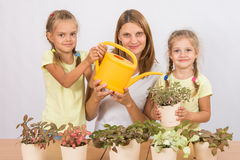 Mother and two daughters caring for potted flowers Royalty Free Stock Photo