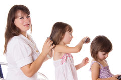 Mother and two daughters combing hair to each othre Stock Image