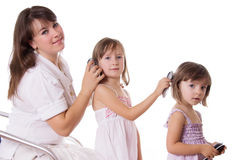 Mother and two daughters combing hair to each othre Royalty Free Stock Images