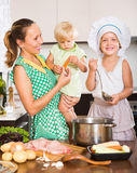 Mother with two daughters cooking Stock Images