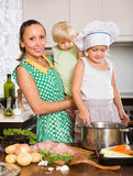 Mother with two daughters cooking Stock Photos