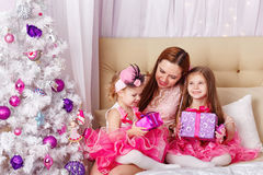 Mother of two daughters gave Christmas presents. Royalty Free Stock Image
