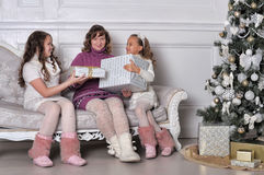 Mother and two daughters with gifts on a sofa Royalty Free Stock Photos