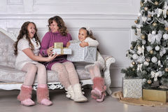 Mother and two daughters with gifts on a sofa Stock Photos