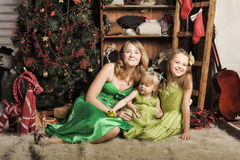 Mother with two daughters in a green dress Royalty Free Stock Image