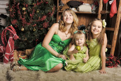 Mother with two daughters in a green dress Stock Photo