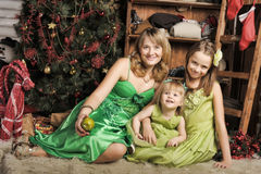 Mother with two daughters in a green dress. At Christmas Stock Photos