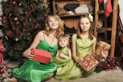 Mother with two daughters in a green dress Royalty Free Stock Photos