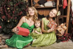 Mother with two daughters in a green dress Royalty Free Stock Images