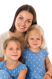 Mother and two daughters. Happy young mother tenderly embraces his beloved daughters who are dressed in identical blue dresses with polka dots. The plan Stock Photos