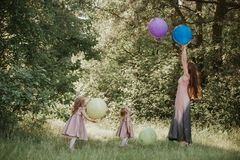 Mother and two daughters holding hands circling. Family time together. Funny time. Girls with balloons. Soft focus stock image