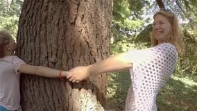 Mother and two daughters hugging thick tree. Girl joking and having fun stock video