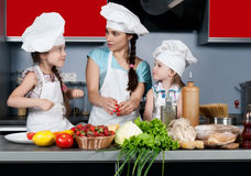 Mother and two daughters in the kitchen Stock Photos