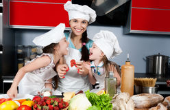 Mother and two daughters in the kitchen Royalty Free Stock Photos