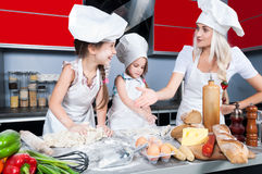Mother and two daughters in the kitchen Stock Image