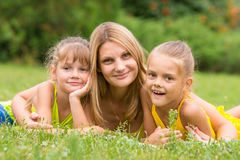 Mother and two daughters lie on green grass, and looked into the frame Stock Images