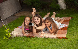 Mother and two daughters making photos of themselves at park Stock Photos