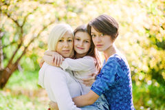 Mother and two daughters in a park Stock Photos