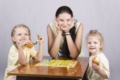Mother and two daughters play a Board game Stock Photography