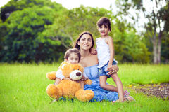Mother and two daughters playing in grass royalty free stock photo
