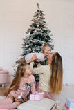 Mother and two daughters playing at at home near Christmas tree. happy family have fun for the Christmas holidays Royalty Free Stock Photos