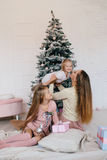 Mother and two daughters playing at home near Christmas tree. happy family have fun for the Christmas holidays Stock Photography