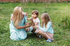 Mother and two daughters playing with a rabbit in the spring garden. stock photo