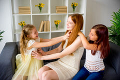 Mother and two daughters playing and tickling. Mom with two daughters playing in the tickle Stock Image