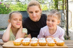 Mother and two daughters salivate looking freshly Easter cupcakes Stock Photos