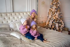 Mother with two daughters sitting on the bed in a sweater. And a warm cap Stock Photos