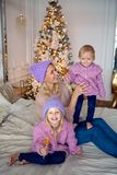 Mother with two daughters sitting on the bed in a sweater. And a warm cap Stock Image