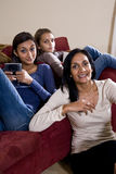 Mother and two daughters sitting at home on sofa Royalty Free Stock Image