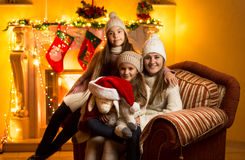 Mother and two daughters sitting on sofa at fireplace at Christm Stock Photo